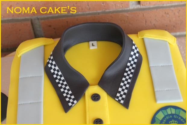 Miriam quería sorprender a su marido con una tarta igual que su camiseta de trabajo. Toda la decoración está hecha con fondant. La placa y los cuadraditos son de papel de azúcar. Por dentro, un bizcocho de naranja relleno de chocolate negro. Equilibra.t@hotmail.com (Noma Cake's, Barcelona)